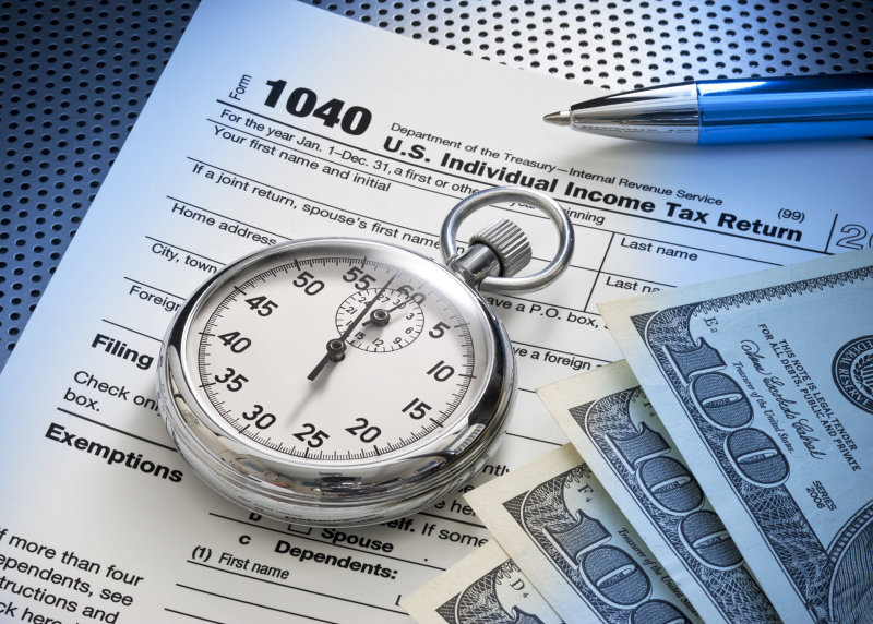 stopwatch clock on top on an income tax return form